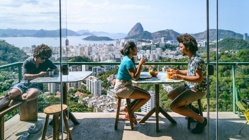 Man and woman on balcony, scenic view and city backdrop, on vacation.