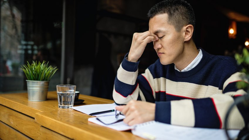 Succesful young japanese freelance worker organizing his time while sitting in a cafe.