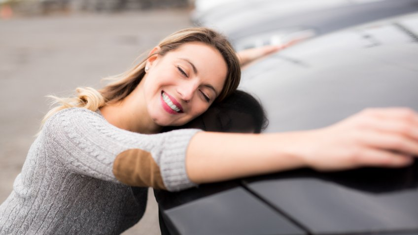 A Jolly young female driver hugging her new car.