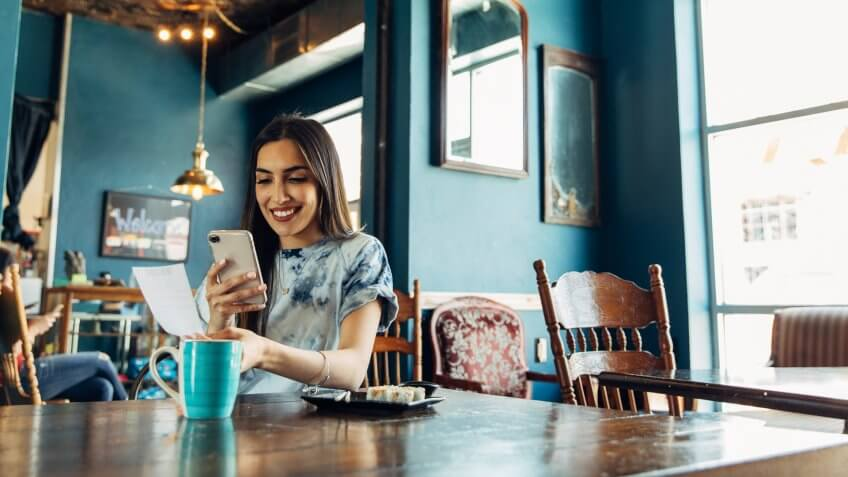 A hispanic woman of the Millennial Generation is taking a picture of a restaurant receipt after eating lunch at a local sushi restaurant.