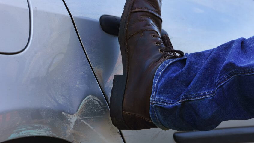 guy kicking car door shut