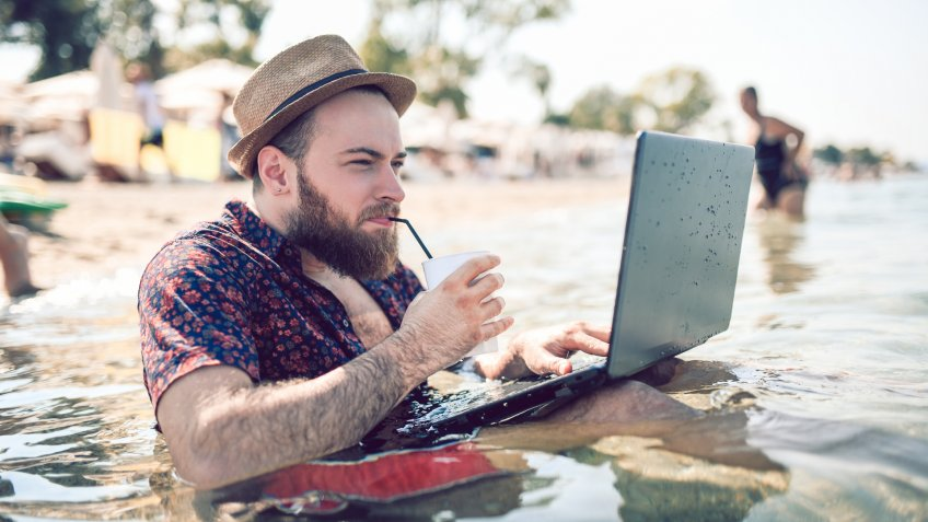 Bearded Guy With Straw Hat Watching Movie On Waterproof Laptop While Drinking Coffee In The Middle Of The Sea.