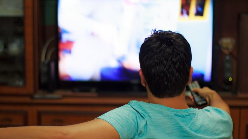 Male watching television in home living room / channel hopping.