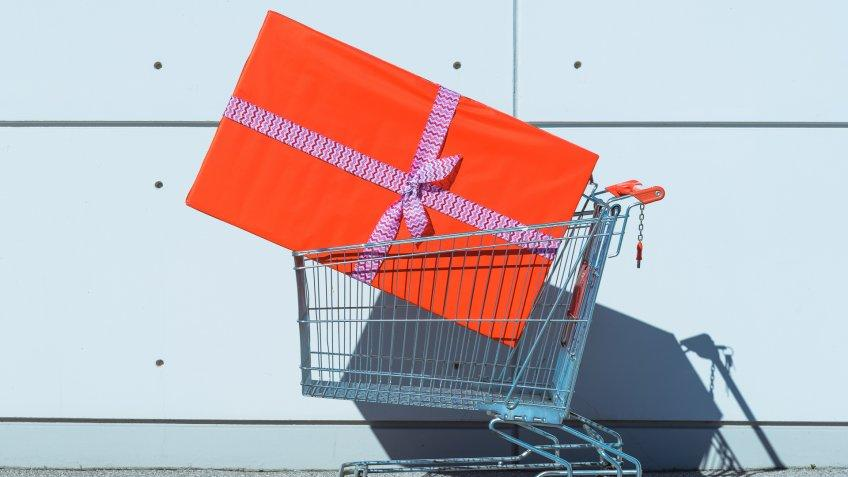 Big red gift box in shopping cart.