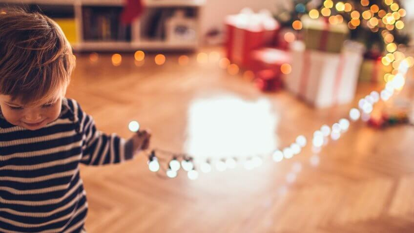 Little boy decorating its first Christmas tree, puting an ornaments and lights on.