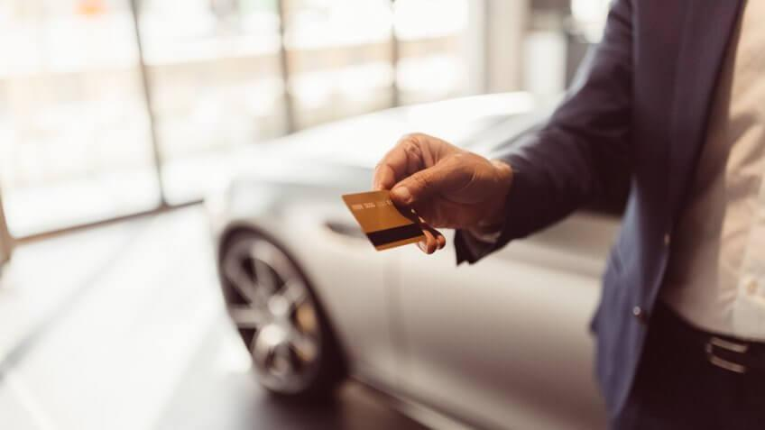 Businessman buying a new car with credit card.