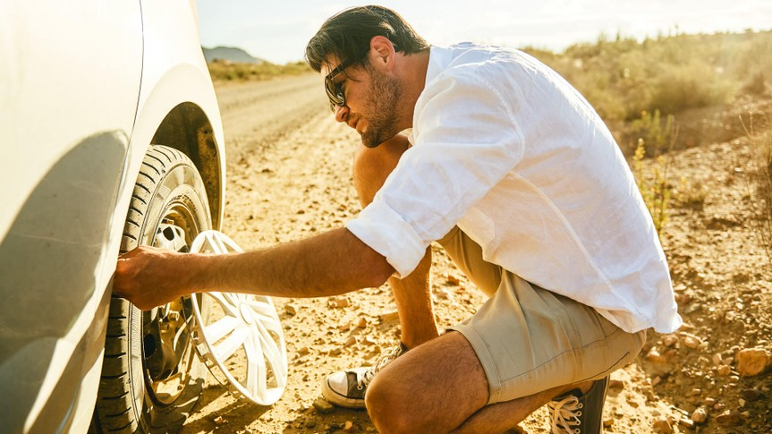 Shot of a young man inspecting a flat tyre on his car in a rural area.
