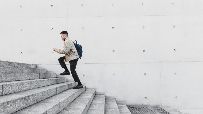Young man running up steps in urban setting.