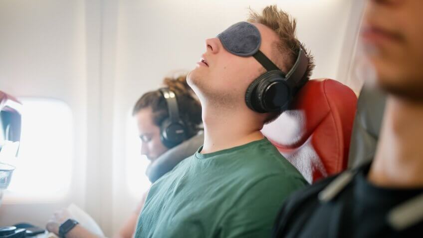 Close up shot of a young man asleep with his head back snoring on a flight in economy class.