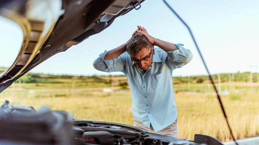 Senior Man examining a broken car on a sunny day.