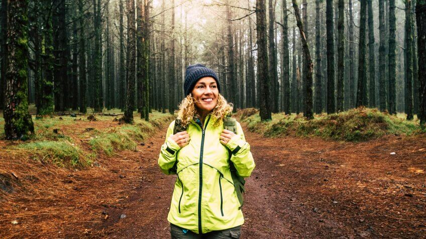 Happy hiker caucasian woman smile and enjoy the nature walking in a forest with high trees - alternative outdoor leisure activity and vacation lifestyle - sun in backlight and mist concept.