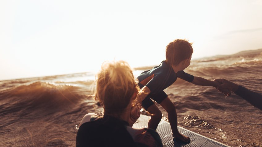 Photo of a cheerful little boy trying to stand up on a surfboard right before the wave strikes with a little help from his mother/ surfing teacher.