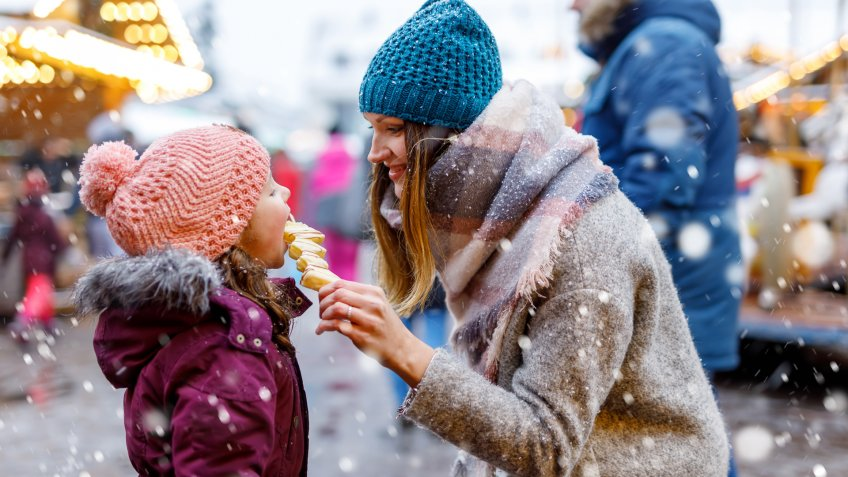 Young mother and daughter eating white chocolate covered fruits on skewer on traditional German Christmas market.