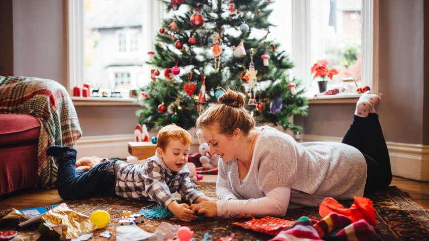 A young mother and her son are celebrating Christmas morning together, they are both lying on the floor and playing with newly opened toys together.