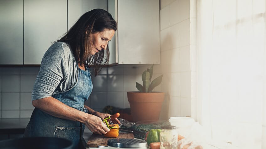 Shot of a mature woman preparing a meal in her kitchen at home.