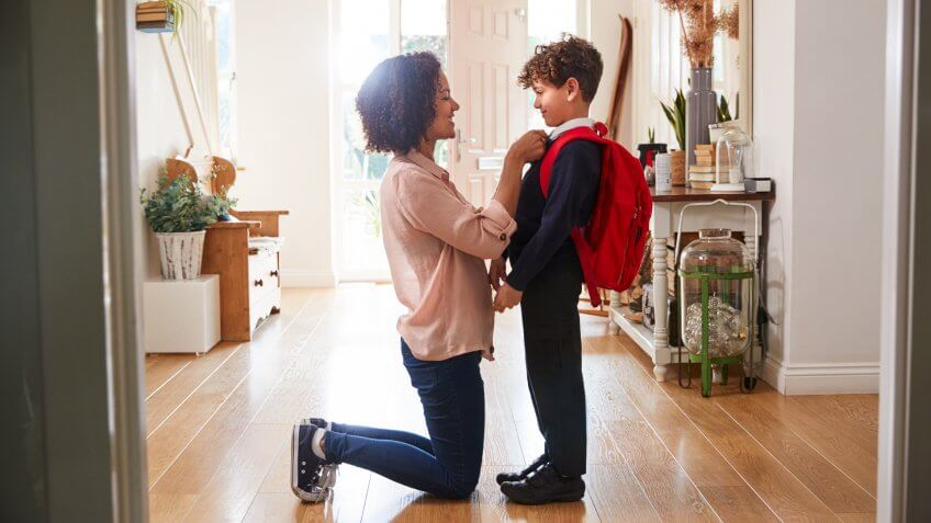 Single Mother At Home Getting Son Wearing Uniform Ready For First Day Of School.