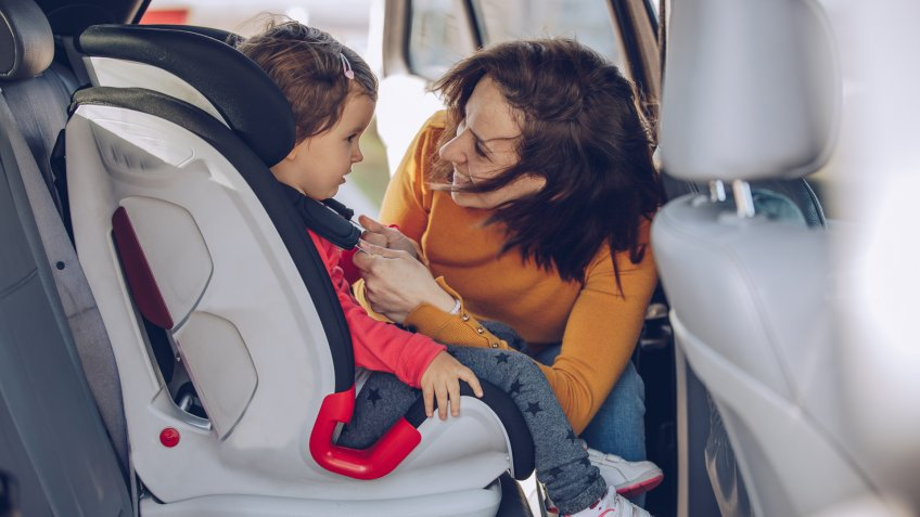 Two girls, single mother buckling up her daughter in a car, traveling together.