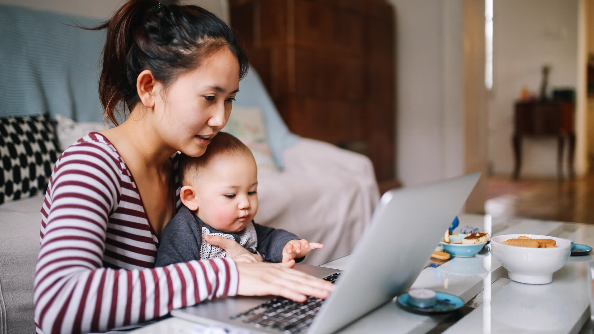 Portrait of a young Asian woman sitting at home, doing some freelance job while taking care of her little baby boy.