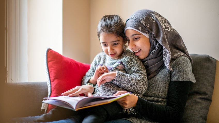 A pre-teen girl wearing a hijab sits on a couch with her little sister on her lap and reads her a bedtime story.