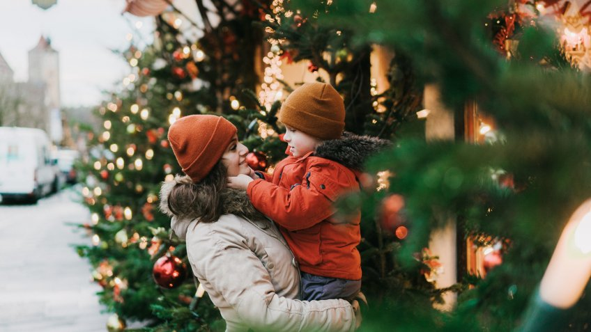 Caucasian mother with preschool son  standing near Christmas tree in Rothenburg.
