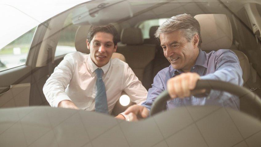 Businessman pointing a car interior at new car showroom.
