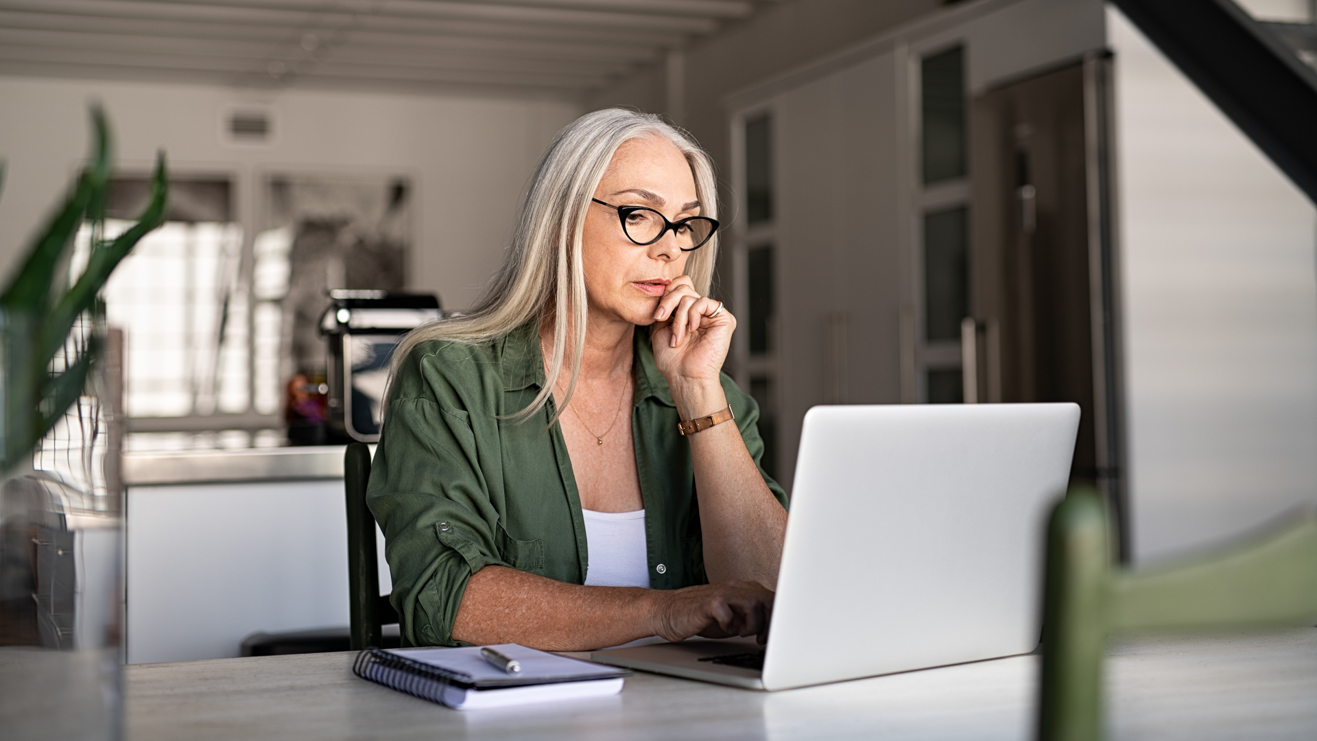 Focused old woman with white hair at home using laptop.