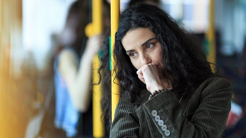 Pensive young woman traveling with bus and holding smart phone.