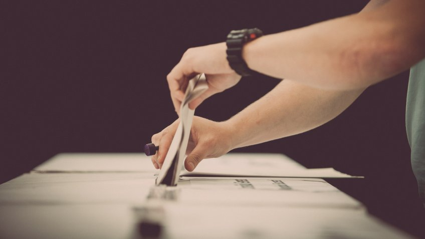 person casting ballot vote on election day