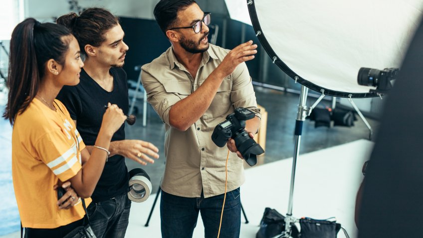 Photographer explaining about the shot to his team in the studio.