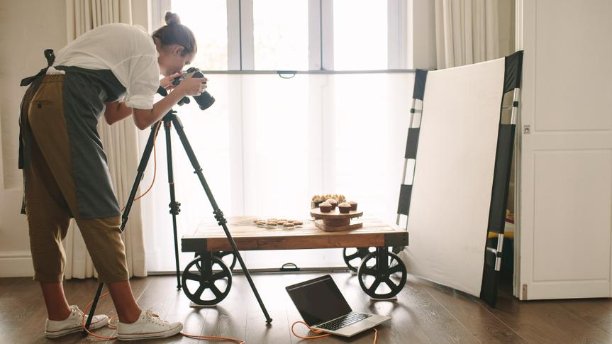 Professional food blogger taking pictures of pastry items on table with dslr camera.