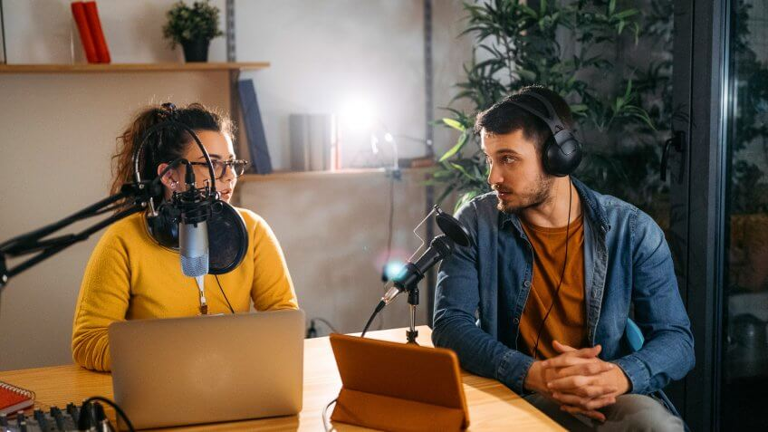 Photo of two young people recording a podcast in a studio.