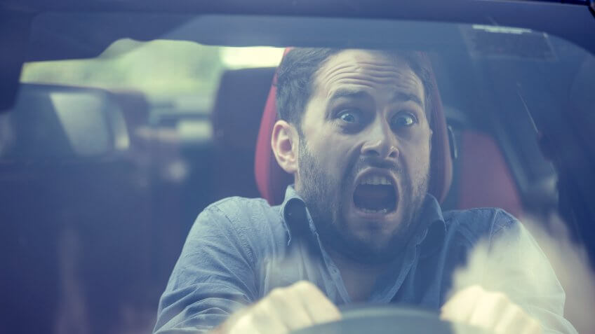 Young man driving a car shocked about to have traffic accident, windshield view.