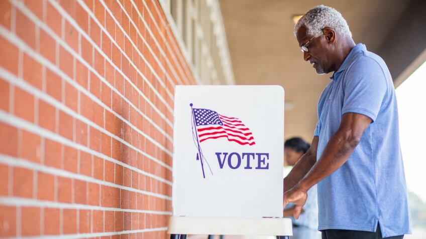 A senior black man casts his ballot on election day.
