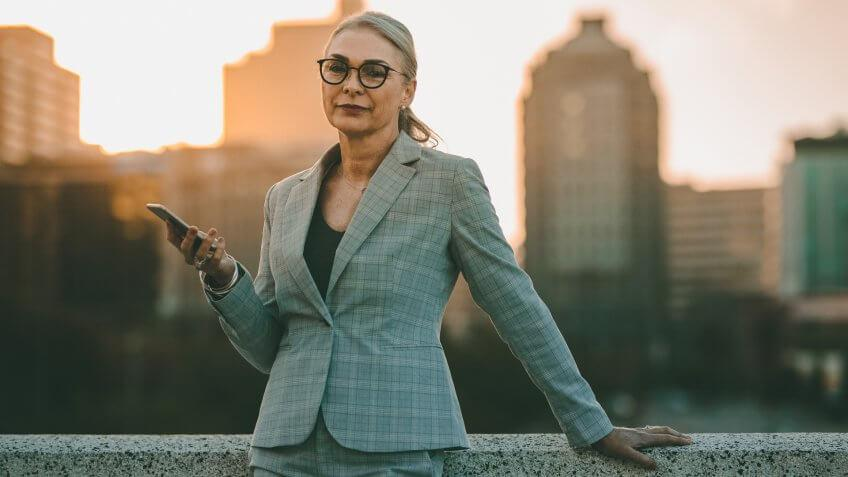 senior businesswoman in suit holding smartphone for work