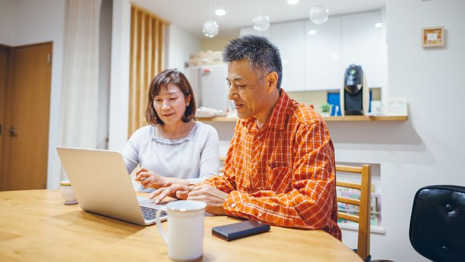 A married senior couple is using laptop at home.