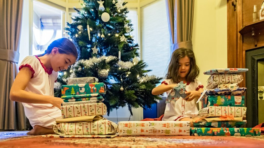 Two smiling young sisters opening wrapped Xmas gifts with morning sun shining through window and Christmas tree in background.