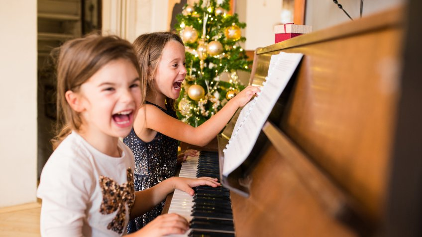Young girls playing with piano at home.