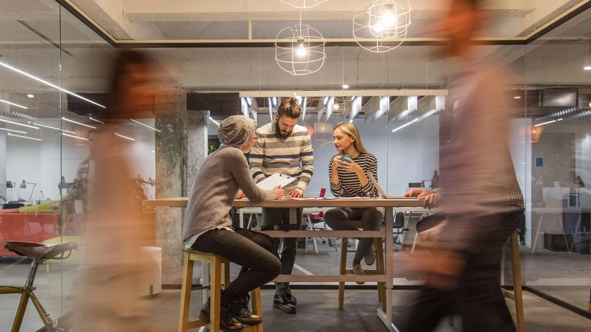 Young entrepreneur having a business meeting inside of an office while their colleagues are walking in blurred motion.