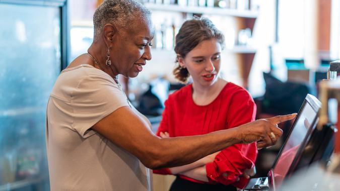 The active senior, 77-years-old, African-American businesswoman, business owner, teaching the new employee, the 18-years-old Caucasian white girl, how to use the computerized cash register in the small local restaurant.