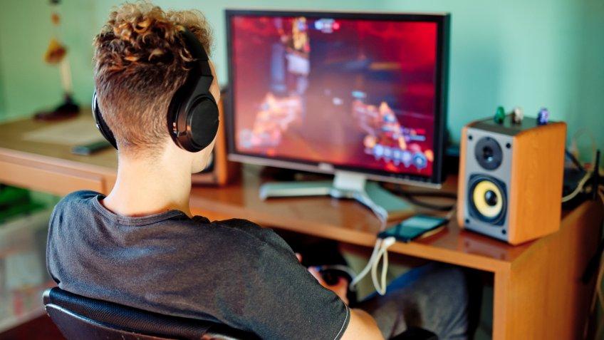 Teen Boy Playing Games on Computer wearing Headphones.