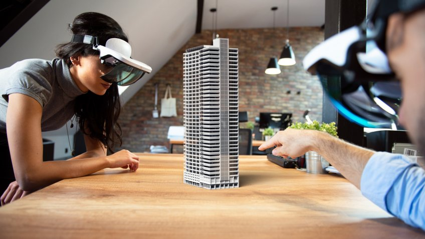 Two people working on virtual 3d building by using AR glasses.