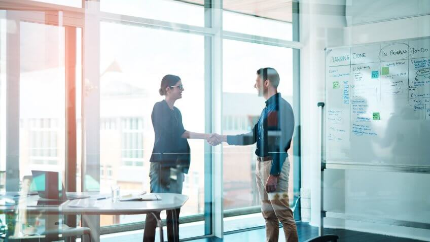 Shot of a businessman and businesswoman shaking hands in a modern office.