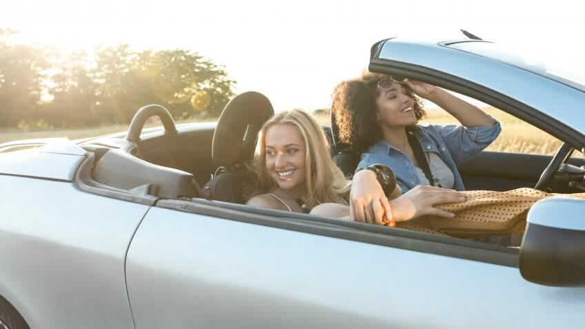 Two beautiful women traveling with a car, laughing ang having fun.