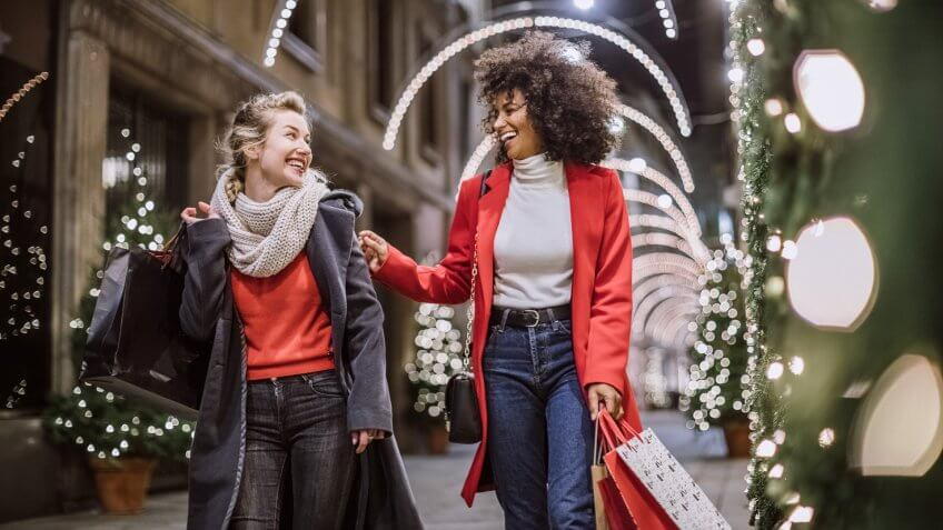 Pretty Young Female Friends Smiling Broadly In Cheerful Manner Having Fun At Shopping Mall, Buying Christmas Gifts.