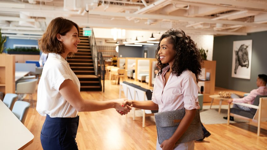 Two Businesswomen Meeting And Shaking Hands In Modern Open Plan Office.
