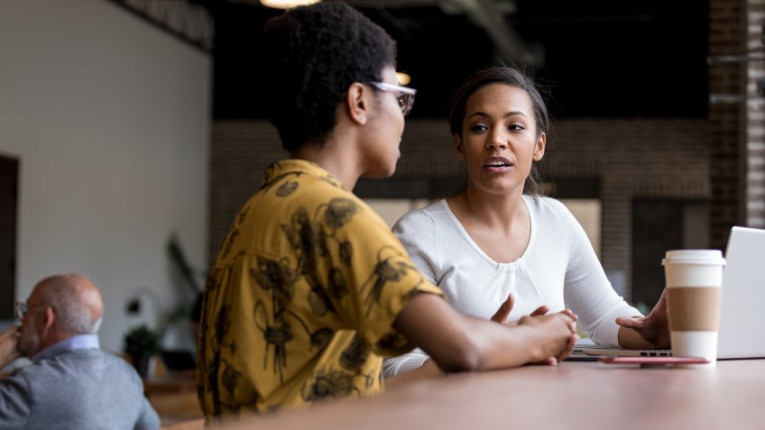 Woman has serious conversation with friend while in coffee shop.