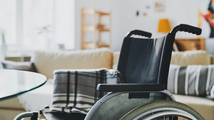 Empty wheelchair dor a disable person with folded plaid on background of big couch with cushions in living-room.