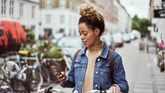 Shot of an attractive young woman using her cellphone while out cycling through the city.
