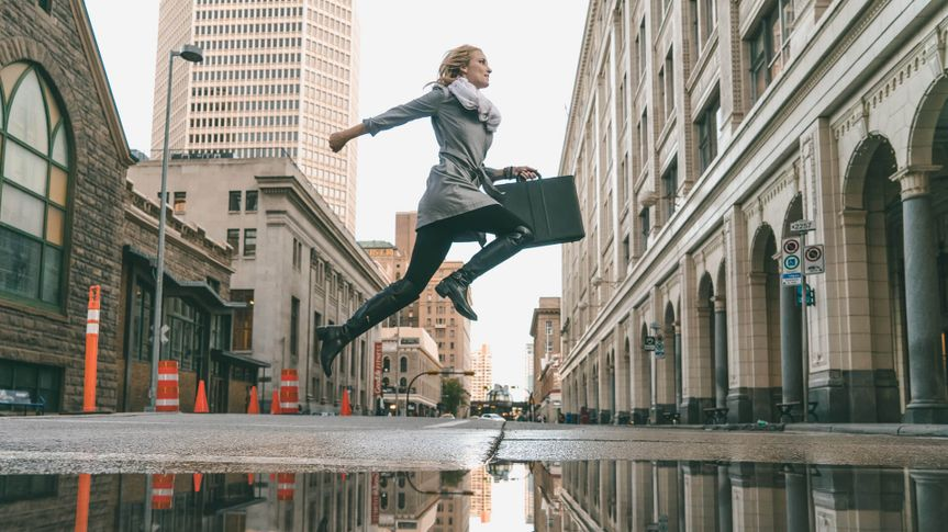 woman jumping with briefcase to work