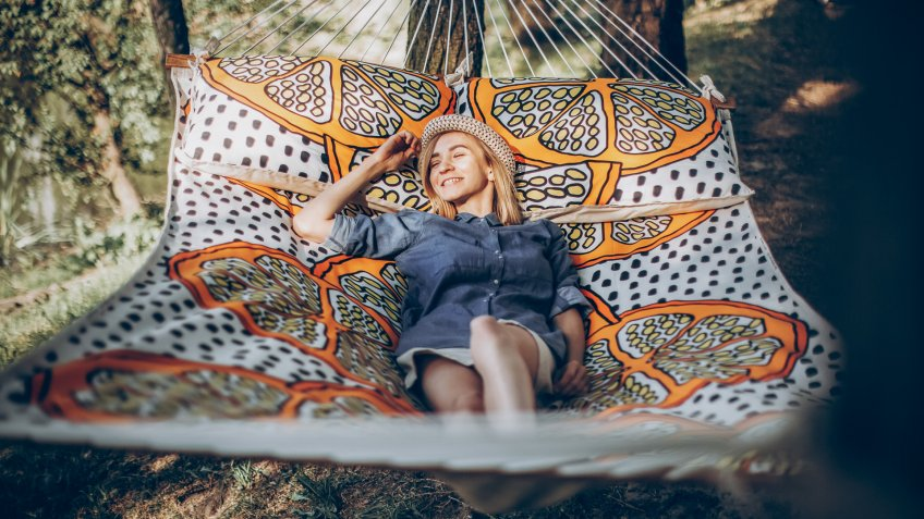 Smiling blonde hipster woman sleeping on a hammock outdoors, beautiful girl in stylish jean clothing relaxing on hammock in the park near a lake, camping concept.
